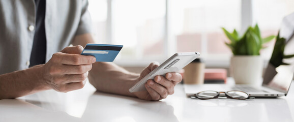 Man holding credit card and using smartphone at office panoramic banner, businessman shopping online, e-commerce, internet banking, spending money, working from home concept