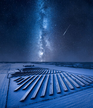 Milky way over frozen photovoltaic farm in winter.