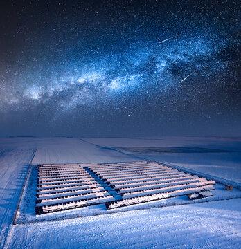 Milky way over snowy solar panels. Alternative energy in Poland