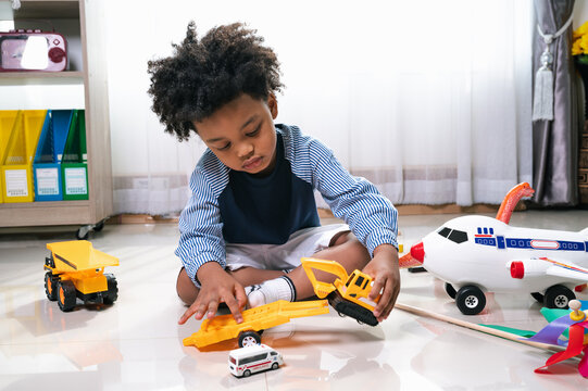 Happy black people African American child play truck and airplane toy at home