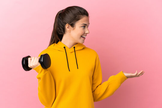 Young sport girl making weightlifting over isolated pink background with surprise expression while looking side