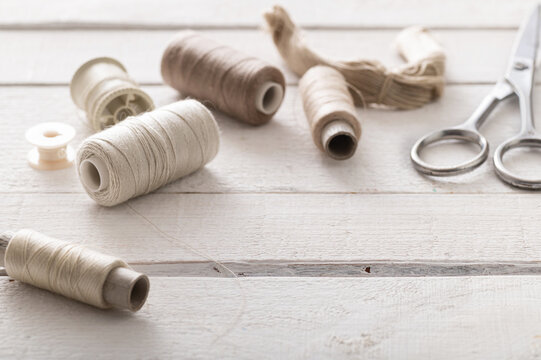 sewing supplies, threads for needlework, scissors, on a white table from wooden boards, close-up