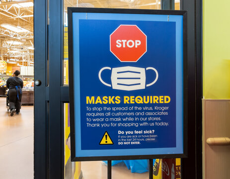 AUGUSTA, GEORGIA - APRIL 2, 2021 : Mask or face covering required sign near entry door of Kroger Grocery Store. Corona Virus (COVID-19) has prompted many retailers to mandate cloth face coverings.