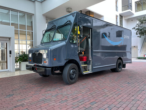 Miami Beach, FL, 3-24-2021: Amazon Prime delivery truck is parked by the entrance to a residential highrise.