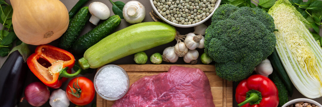 Fresh farm organic vegetables banner, healthy food concept, vegetables and mushrooms, superfoods and beans around the board with a large fresh piece of beef fillet, top view