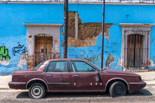 Broken down old car in front of weathered colourful building façade in the city of Oaxaca in Mexico