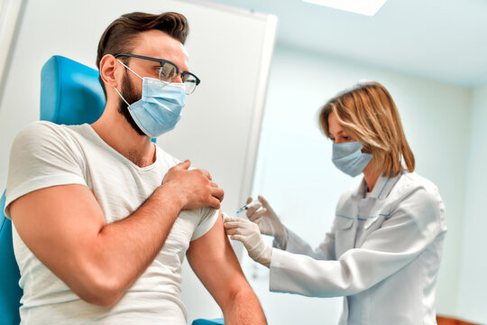 Vaccination, immunization campaign, disease prevention concept. Young man in medical face mask getting Covid-19 vaccine at doctor's office. Professional nurse giving flu injection to patient