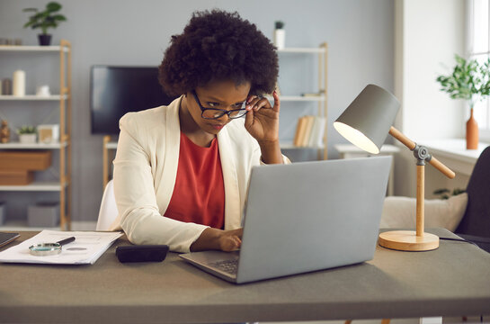 Young african american woman in eyewear carefully reading text on laptop computer device screen or typing answer on received letter, analyzing annual report sitting at desk in office. Business and job