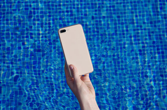 Clear phone case mockup in hand on the background of the swimming pool smartphone back view