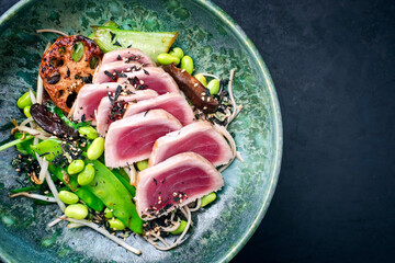 Modern style traditional Japanese gourmet seared tuna fish steak tataki with soba noodles and stir-fried vegetables served as top view on a Nordic design bowl with copy space right