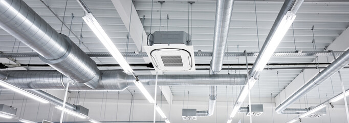 Fototapeta Ceiling mounted cassette type air condition units with other parts of ventilation system (tubes, cables and vents) located inside commercial hall with hanging lights and other construction parts. obraz