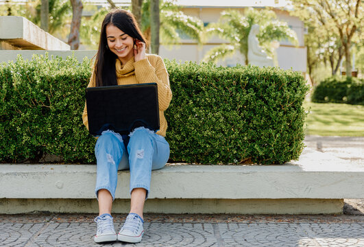 Latina girl with computer smiling in public park. working on computer outdoors.