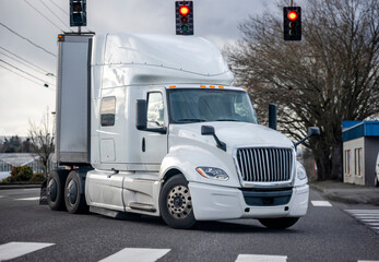 Powerful bonnet white big rig semi truck with dry van semi trailer turning on the city street crossroad with traffic light and crosswalk