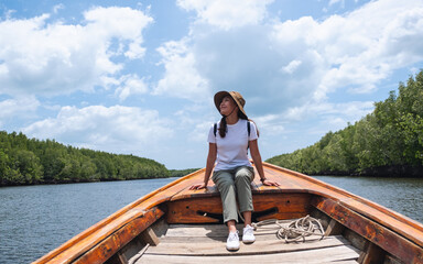 Portrait image of a beautiful young asian woman sitting on a long tail boat while traveling the sea and mangrove forest