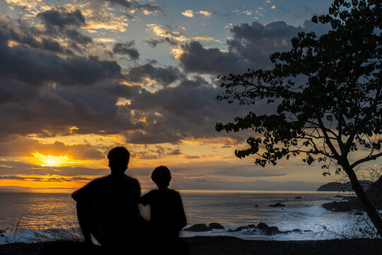 Beautiful picture of Father and son  watching the sunset in the pacific ocean in the magical beaches of Costa Rica