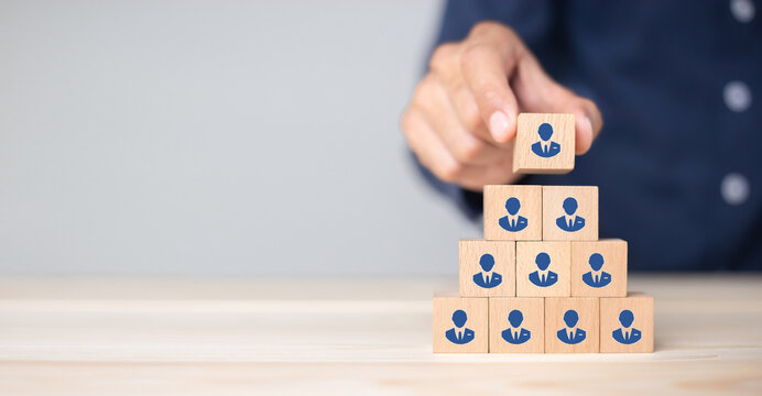 Concept of human resource management and recruitment business Hand put wood cube block on top pyramid To business success concept.