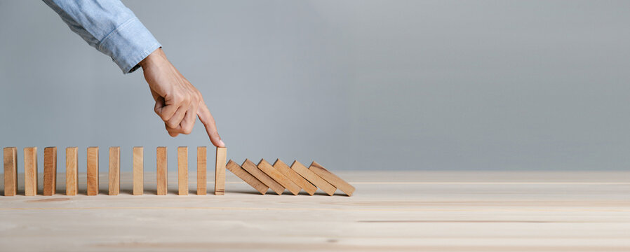 Businessman hand stopping the domino wooden effect concept for Planning,risk and strategy in business.