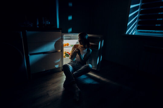 a hungry girl sits with her elbows on an open refrigerator holding a bottle of milk in her hands. The image was shot in a low key to convey night time.