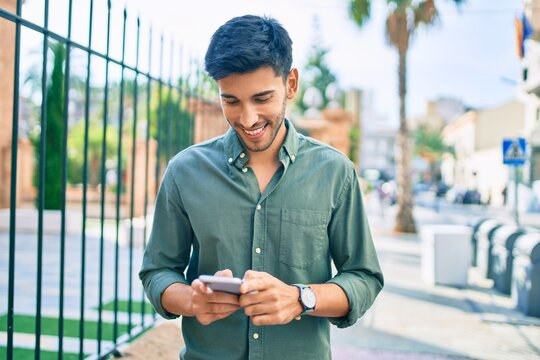 Young latin man smiling happy using smartphone walking at the city.
