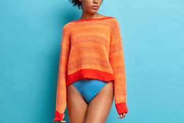 Obraz Rear view of slim woman wears long sleeved orange jumper and panties has long legs fit smooth skin fit figure models against blue studio background - fototapety do salonu