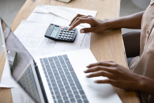 Close up view of African American woman sit at table work on laptop calculate finances on machine. Biracial female manage budget care of expenses expenditures pay online on computer. Save concept.