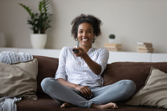 Overjoyed millennial African American female renter relax on couch in living room watch TV online. Happy young biracial woman rest on sofa at home have fun enjoying television program. Hobby concept.