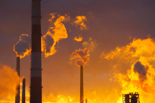 Environmental pollution. Factory pipes. Sunset background