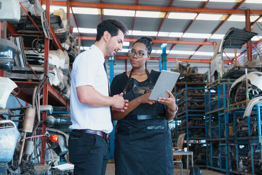 Women show autopart on tablet to man. Diversity of two people, caucasian business manager work with African worker woman in factory-warehouse