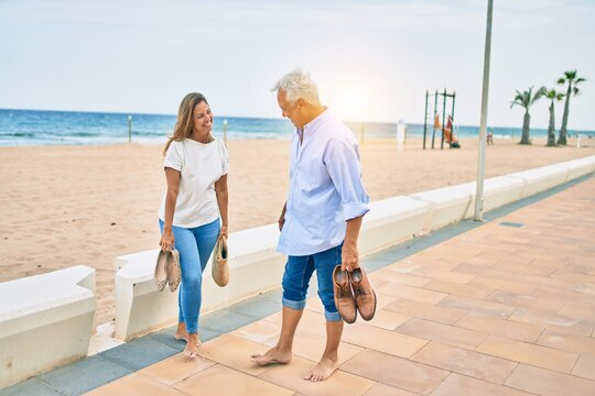 Middle age hispanic couple smiling happy walking at the promenade