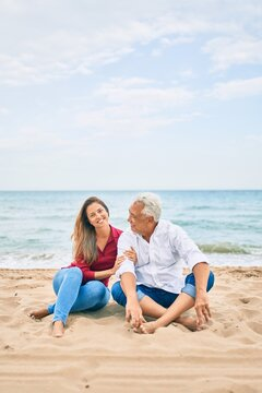 Middle age hispanic couple smiling happy and hugging sitting at the beach