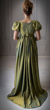 A young Regency woman wearing a green shot silk dress and viewed from behind