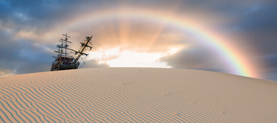 Silhouette of old ship on desert with rainbow at amazing sunset