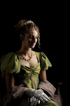 A young Regency woman wearing a green shot silk dress and a tiara posing against a black backdrop