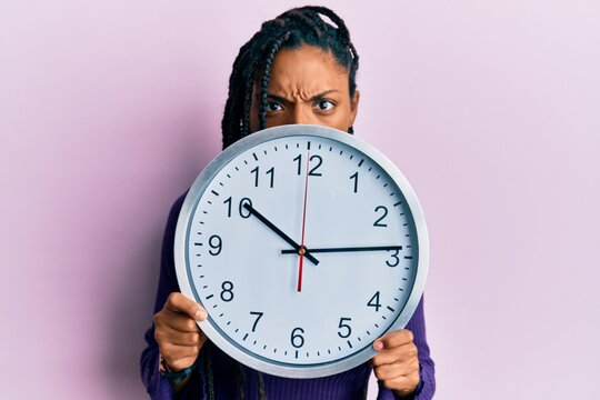 African american woman with braids holding big clock covering face skeptic and nervous, frowning upset because of problem. negative person.