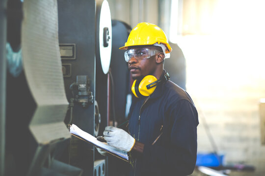 Quality control inspector checking workers at factory. Engineering Worker team working in Heavy Industry Manufacturing Facility. Engineer Operating lathe Machinery. American African people.
