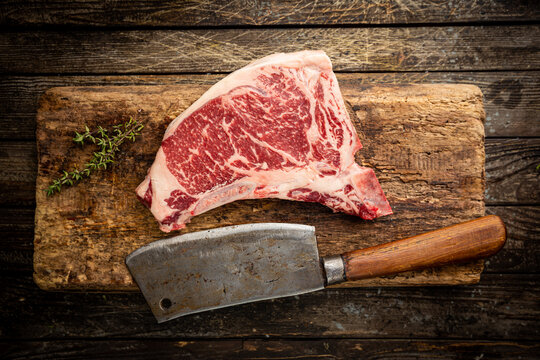 Raw fresh meat T-bone beef Steak and butcher knife on wooden background, top view