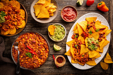 Mexican food concept: tortilla chips, guacamole, salsa, chilli con carne and fresh ingredients over wooden background, top view