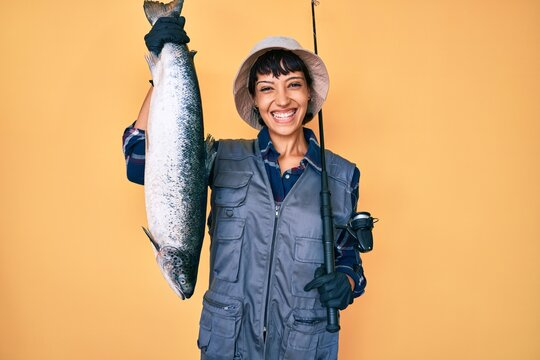 Beautiful brunettte fisher woman holding fishing rod and raw salmon smiling with a happy and cool smile on face. showing teeth.