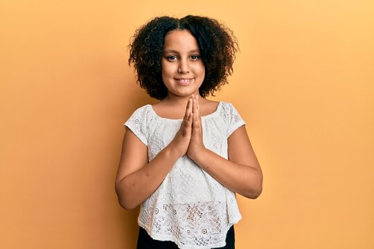 Young little girl with afro hair wearing casual clothes praying with hands together asking for forgiveness smiling confident.