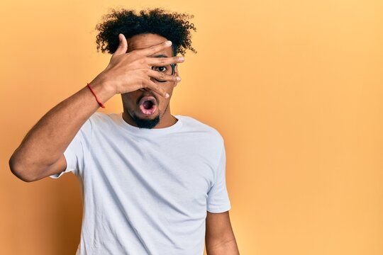Young african american man with beard wearing casual white t shirt and glasses peeking in shock covering face and eyes with hand, looking through fingers afraid