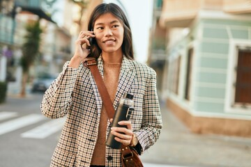 Fototapeta Young asian businesswoman smiling happy using smartphone at the city.