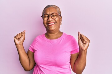 Obraz Senior african american woman wearing casual clothes and glasses very happy and excited doing winner gesture with arms raised, smiling and screaming for success. celebration concept. - fototapety do salonu