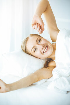 Happy woman stretching hands in bed after waking up, entering a day happy and relaxed after good night sleep. Sweet dreams, sunny morning concept
