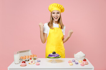 Teen fun girl chef cook confectioner baker in yellow apron cap at table do winner gesture clench fist celebrating isolated on pastel pink background. Mousse cake cooking food process workshop concept.