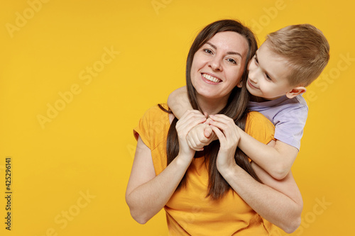 Happy young woman have fun with cute child baby boy 5-6-7 years old in violet t-shirt. Mommy little kid son posing together hugs isolated on yellow background studio. Mother's Day love family concept.