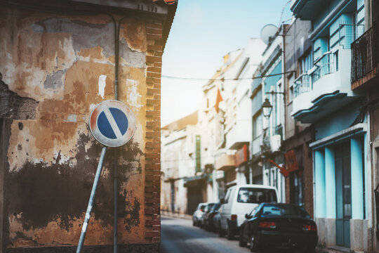 """View of a narrow street of a small European town with cars and a shallow depth of field with selective focus on the foreground with a yellowish peeled house wall with a lopsided """"no parking"""" road sign"""