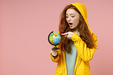 Redhead young woman 20s in yellow waterproof hood raincoat outerwear holding in hands spin Earth world globe isolated on pastel pink background studio portrait. Outdoors lifestyle fall season concept