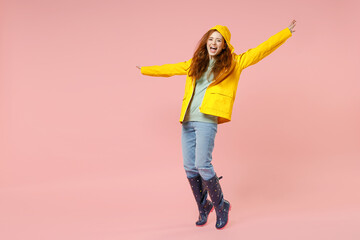 Full length redhead young woman in yellow waterproof raincoat outerwear stand on toes dancing leaning back isolated on pastel pink background studio Outdoors lifestyle wet fall weather season concept.
