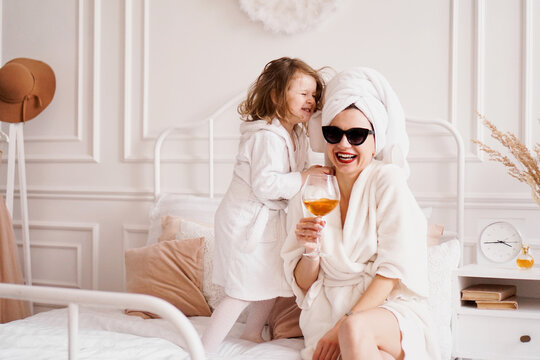 Mother and daughter in the bedroom in bathrobes. Happy daughter is jumping