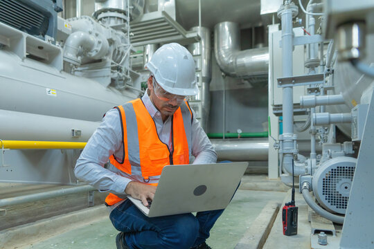 An engineer man or worker, people using a laptop computer, working in industry factory. Chiller tower or cooling tower in building. System work machine. Condenser Water Supply pipe lines. Ventilation.